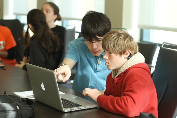 A mentor pointing out something on a student's laptop screen